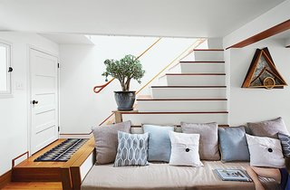 In the living room, the stair's lower step reaches out to form an arm, while the ascending stairs create a natural incline for cushions.