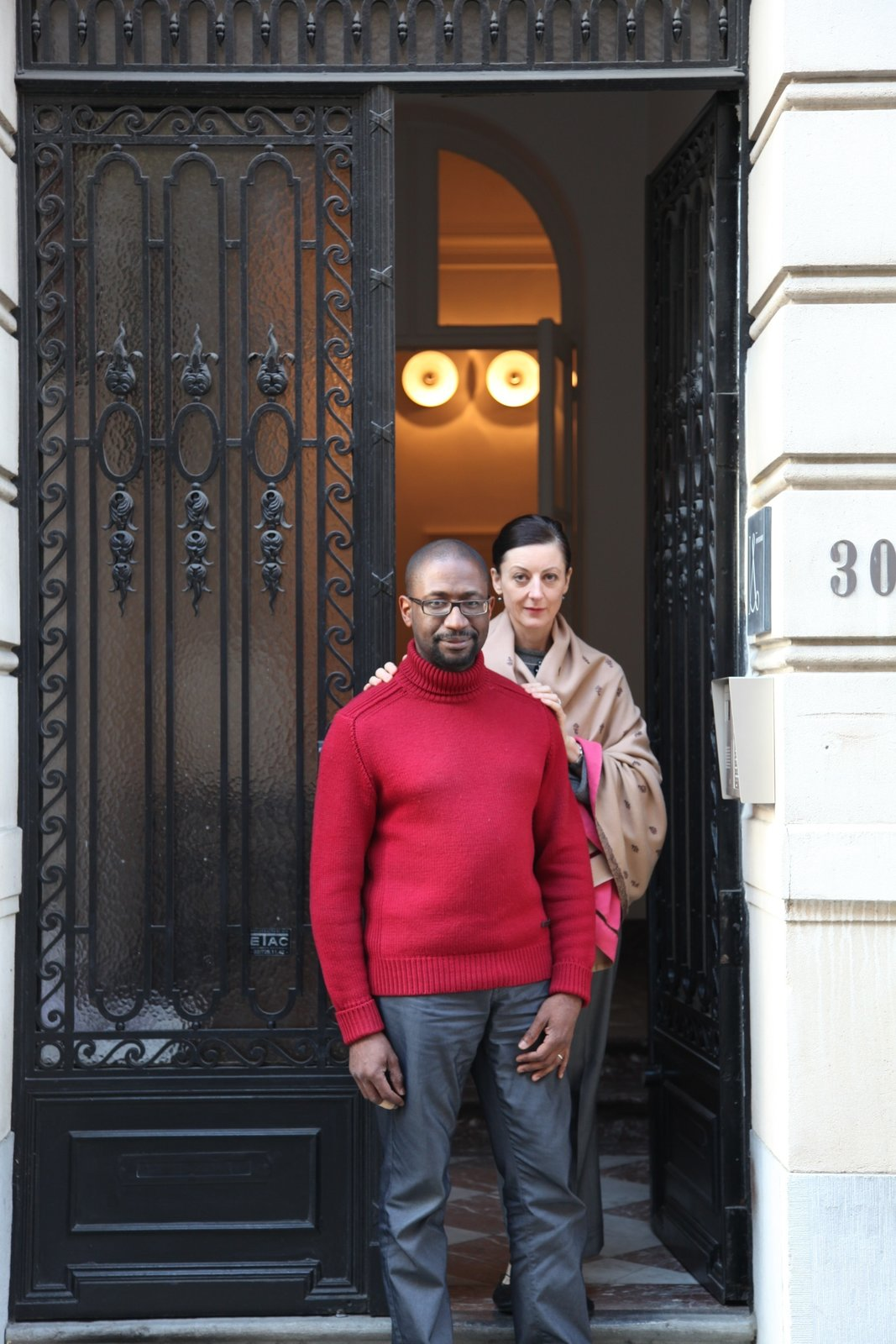 """Udechuku and Smith stand in front of their neoclassical townhouse in Brussels. They met at law school in Australia (Smith is Australian, Udechuku is British) and together discovered their love of design while furnishing their homes over the years—in Australia, in London, in San Francisco, and later in Luxembourg. Today, clients come to them """"for the breadth of our design knowledge, relentless pursuit of perfection for each client, and for our ability to research and source rare and unusual pieces,"""" says Udechuku.  Photo 14 of 18 in A Neoclassical Gallery Home in Belgium"""