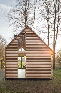 The house may appear conventional at a glance, but a closer look shows how Oostenbruggen has pushed the boundaries of the traditional gabled typology. It has an asymmetrical roof, with slate shingles that extend down the eastern side to close it off completely.