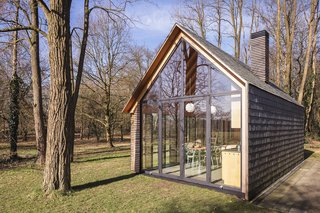 "For this Dutch collaboration between Zecc Architects and designer Roel van Norel, building on top of the foundation of what used to be a greenhouse was a cost-cutting measure. Built in a forest north of Utrecht, the tiny cabin lets the owners ""flee daily life"" while taking in as much or as little of nature as they like."