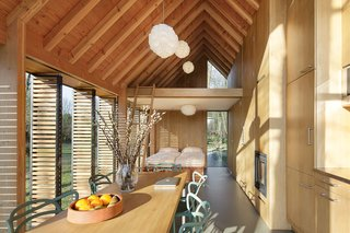 The house's open plan is neatly divided into public and private spaces, with the front containing the kitchen and living areas and the back holding the bedroom and bath, overhung by a small mezzanine. A hidden wooden panel can be drawn closed between the two sections for greater privacy.