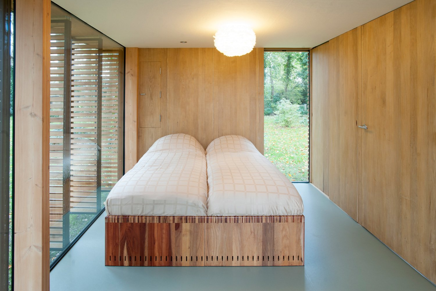 Bedroom, Bed, and Ceiling Lighting Light breaks through the bedroom's north wall through a vertical window that cuts from the floor up past the second floor mezzanine to the roof's ridgeline. The bed is custom.  Photo 5 of 9 in This Light-Filled Cabin in the Netherlands Is Completely Made by Hand from Utrecht Cabin