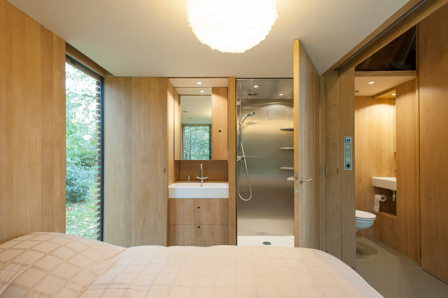 Bath Room and Enclosed Shower In the bedroom, a door opens directly to the stainless steel shower. A half-bath sits just outside the bedroom, allowing guests easy access to it when the wood panel dividing the bedroom from the main area is drawn. The sinks are by Duravit and faucets by Grohe.  Photo 6 of 9 in This Light-Filled Cabin in the Netherlands Is Completely Made by Hand from Utrecht Cabin