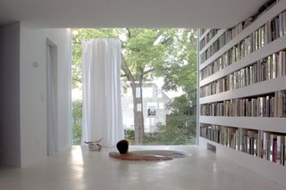 This studio replaced a single-story garage, which was demolished. Its ground level still serves as a carport, but the upper levels now house a library and reading room. The studio's second floor serves as a library. The sunken bathtub offers interrupted sight lines across the space and out into the backyard. The tub, like the library's floor, is made of concrete.