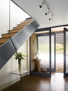 In homes that aren't short on square footage, the space under a staircase can be the perfect spot to create a beautiful ensemble of items like a grouping of your favorite vases or a special piece of furniture. In this home near Bristol, England, that was designed by Paul Archer, the space under a stairway was made visually, if not programmatically, useful by locating a glass table and vase with simple lines to create a subtle, minimalist vignette.