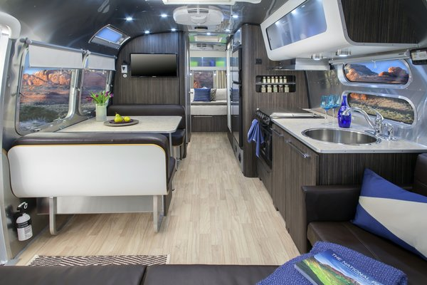 The 28-foot Airstream International Series features interiors by Christopher C. Deam; it sleeps up to six people and includes camping chairs, a gas grill, kitchen amenities, and bike rack.