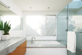 8 Inspiring Minimalist Bathrooms - Photo 1 of 7 - The minimalist bathroom of actress, Glee star, and Los Angeles resident Jayma Mays boasts Cararra marble surfaces, Hansgrohe faucets and shower fixtures, and a skylight by Velux.