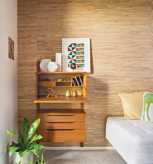 """A Good Reed<br><br>The most changed area of the home is the small guest room–office, where Neely, who works from home, removed the closet doors and added a grass-cloth wall treatment to distinguish it from the rest of the house's decor. """"Many of the Eichlers originally had grass cloth as a covering on the sliding closet doors,"""" he says. """"The guest room–office is the only other room that can be seen from the public areas across the atrium, and I wanted this wall to add visual interest."""""""