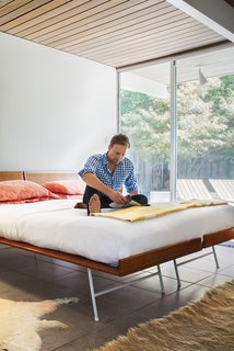 """Full Nelson<br><br>The bed in the master bedroom is actually two single 1950s George Nelson Thin Edge beds--made from birch, enameled metal, and cane--that Neely bought at auction at the John Toomey Gallery in Oak Park, Illinois. """"I love the contrast of the white wall with the wood and woven material,"""" says Neely, who likes to keep the beding simple--often a paisley from Ralph Lauren--so as not to detract from the bed's strong lines."""