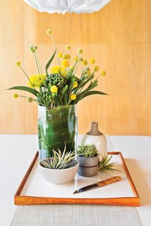 """Full Bloom<br><br>The white Vico Magistretti dining table is a focal point when you enter the house--""""and a great spot to create assemblages of some of my favorite objects,"""" says Neely, who changes the display every few weeks. Set atop a reversible Finn Juhl tray are ceramics from Heath and a Carl Auböck fruit knife with a cane-wrapped handle. Notes Neely:""""I always keep a handful of tillandsia around--air plants soften and warm up the space."""""""