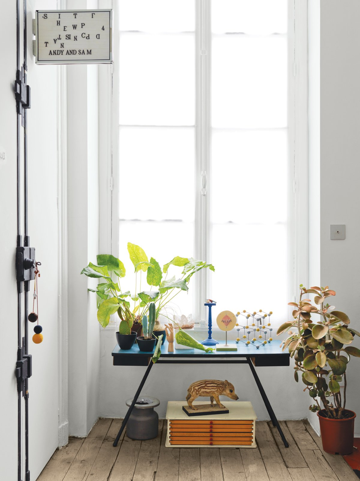 Windows and Wood Vignettes show off what Aumas does best. In this one, he takes advantage of the apartment's tall windows.  Photo 11 of 12 in A Furniture Collector's Renovated Flat in Paris