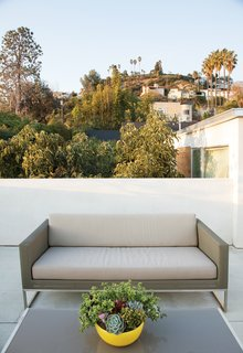 Jacobs transformed the roof into a series of decks, this deck features Crate & Barrel's Dune sofa and coffee table.