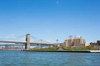 The Brooklyn Bridge Park's greenery encroaches on the East River.