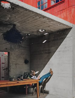 Kiyoko Loh relaxes inside a concrete structure, one of three original buildings that occupied the San Francisco property she and her husband, Elliot Loh, purchased in 2012. Working with architect Todd Davis, the couple decided to cut the bunker-like edifice in half and use it as an outdoor dining area that opens to a courtyard.