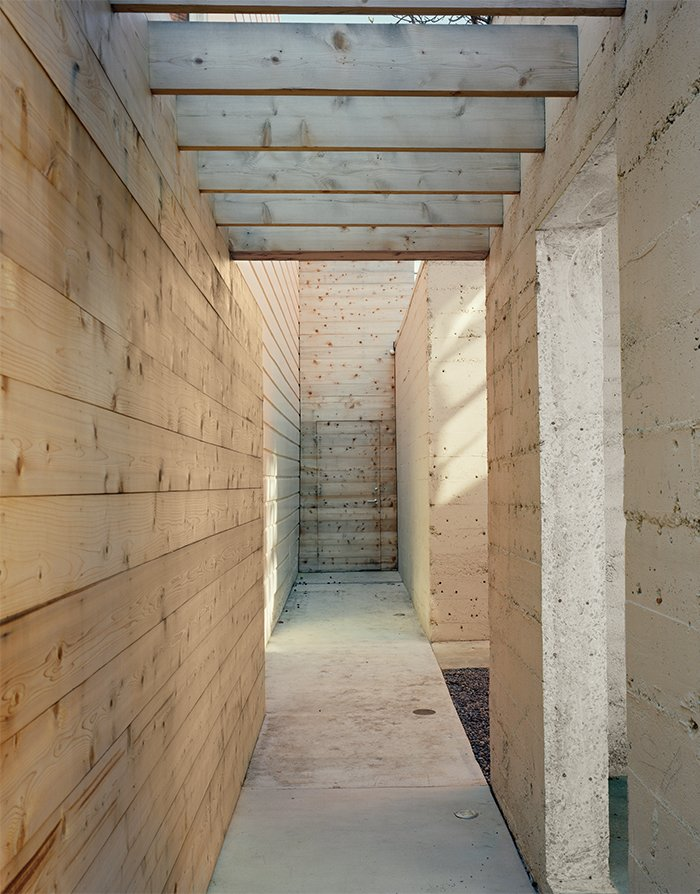 Hallway and Concrete Floor Once inside the property, a cedar-clad walkway runs parallel to the open concrete pavilion.  Photo 9 of 11 in Abandoned Industrial Compound Becomes a Modern Home Base