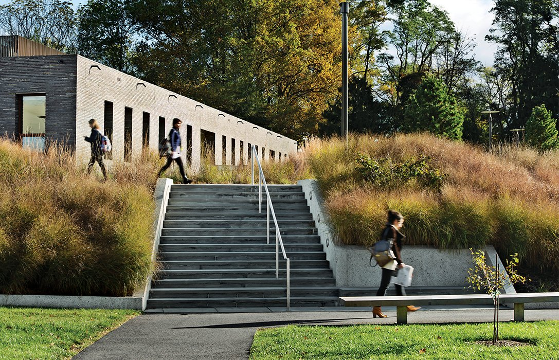Exterior, Brick Siding Material, Stone Siding Material, and Concrete Siding Material Making use of a sculpted berm, Tod Williams Billie Tsien Architects built identical 21,500-square-foot dormitory buildings at Haverford College without interior stairwells or elevators, freeing up room for courtyards and more generously sized common spaces.  Photo 9 of 11 in 11 Innovative and Modern Schools Where Creativity and Good Design Rule from Cutting-Edge Dorms Embrace The Landscape with No Need for Elevators or Interior Stairs
