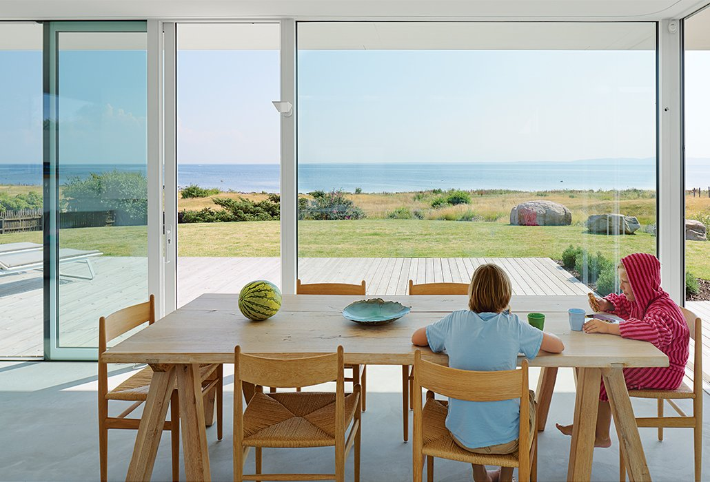 Dining Room and Table Oskar and Karl, 12 and 9, share breakfast at their family's summer getaway in Sweden. The table is from ILVA, and the CH36 chairs by Hans Wegner are from Carl Hansen & Søn.  Photo 8 of 20 in Pull Up a Chair in One of These 20 Modern Dining Rooms from A Scandinavian Summer Home Built for Surf, Sports, and Sun