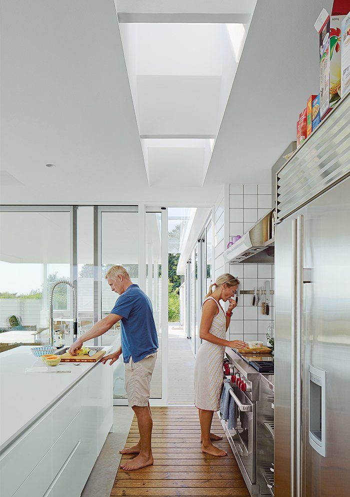 Kitchen, Light Hardwood Floor, and Refrigerator In the kitchen, the couple prepare a meal. The Multiform island is topped in Corian; the oven and hood is from Wolf.  Photo 4 of 10 in A Scandinavian Summer Home Built for Surf, Sports, and Sun