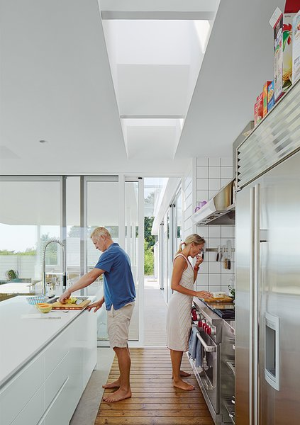 In the kitchen, the couple prepare a meal. The Multiform island is topped in Corian; the oven and hood is from Wolf.  Photo 4 of 10 in A Scandinavian Summer Home Built for Surf, Sports, and Sun