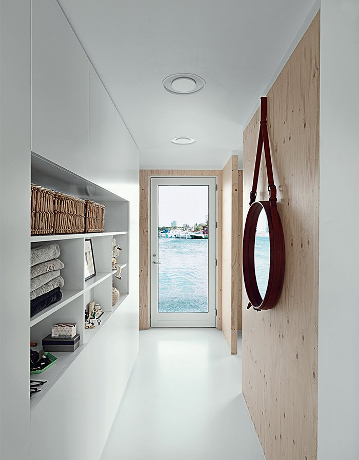 The narrow entrance hall faces another door, which opens seaward. Built-in cabinets serve as both storage and display. The porthole mirror is by Jacques Adnet. Tagged: Doors, Swing Door Type, and Interior.  Photo 2 of 9 in Each Day at This Floating Home Begins With a Swim, Just Two Feet From Bed