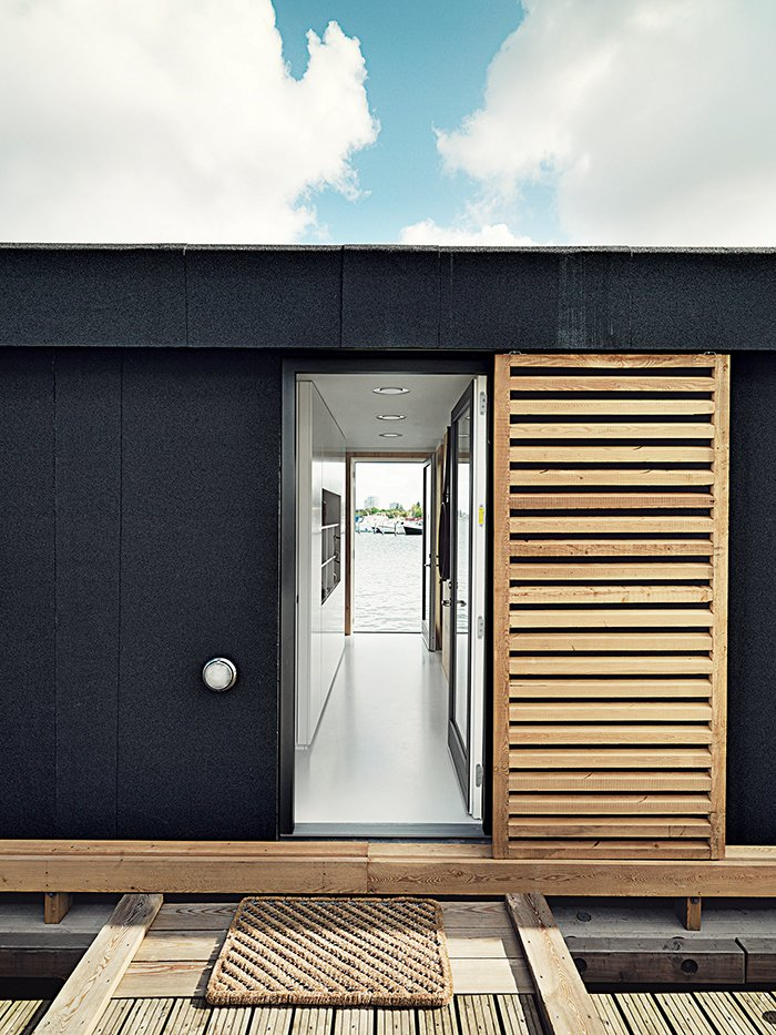 Doors, Sliding Door Type, Wood, and Exterior Outside, larch-wood shutters offer the residents privacy.  Photo 3 of 9 in Each Day at This Floating Home Begins With a Swim, Just Two Feet From Bed