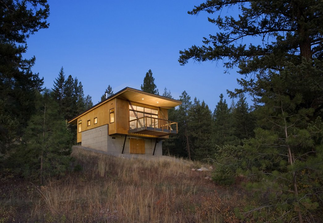 Exterior, House Building Type, Cabin Building Type, Shed RoofLine, Concrete Siding Material, and Wood Siding Material While it was tempting to embed the cabin into the hillside, Balance Associates sought a smarter solution. By elevating the project on two concrete walls, the clients could avoid a costly foundation, improve their view of the landscape, and stay above the thick winter snowfall.  Photo 42 of 101 in 101 Best Modern Cabins from Simple Cabin Embraces Its Mountain Setting
