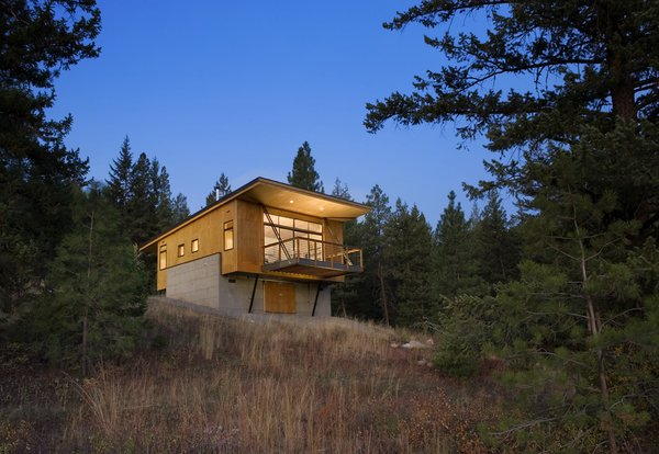 Exterior, Cabin Building Type, and Wood Siding Material While it was tempting to embed the cabin into the hillside, Balance Associates sought a smarter solution. By elevating the project on two concrete walls, the clients could avoid a costly foundation, improve their view of the landscape, and stay above the thick winter snowfall.  Photo 9 of 10 in 11 Hillside Homes That Feature a Balancing Act With Nature