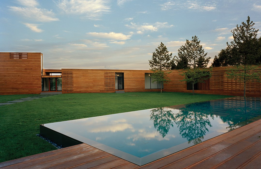 """Outdoor, Large Pools, Tubs, Shower, Wood Patio, Porch, Deck, and Grass As the facade of a Bates Masi-designed home in Water Mill, New York, rises from eight to 14 feet high, the mahogany planks subtly widen. """"It was quite a demand to make of the contractor,"""" architect Paul Masi says. """"But the design was so much about traveling through the site and weaving [the house] together with the deck.""""  Photo 1 of 9 in Modern Wood-Lined Family Home in the Hamptons"""