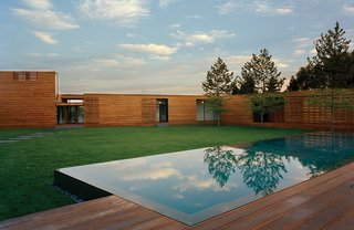 """As the facade of a Bates Masi-designed home in Water Mill, New York, rises from eight to 14 feet high, the mahogany planks subtly widen. """"It was quite a demand to make of the contractor,"""" architect Paul Masi says. """"But the design was so much about traveling through the site and weaving [the house] together with the deck."""""""