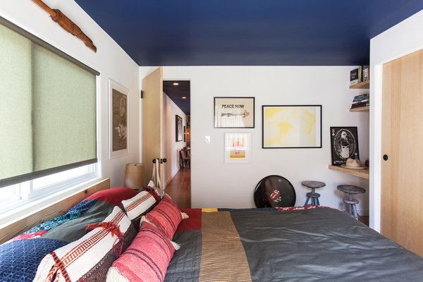 """The blue ceiling continues into the bedroom, filled with art by Howard's friends. The yellow-and-white poster is by Mike Mills, and the signed Rolling Stones drumhead was a gift. """"It feels like a New York apartment at the beach,"""" says Shumate."""