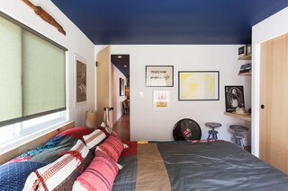 "The blue ceiling continues into the bedroom, filled with art by Howard's friends. The yellow-and-white poster is by Mike Mills, and the signed Rolling Stones drumhead was a gift. ""It feels like a New York apartment at the beach,"" says Shumate."