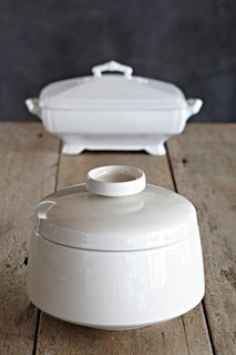 """Since the late 1600s, the tureen has held an important place on the table. To quote Alice in Wonderland, 'Beautiful soup, so rich, and green/Waiting in a hot tureen.' A century apart, these two white tureens, one in the Eva Zeisal style and the other an English classic from the 19th century, are ready set to serve green beans, pilaf, or a massive amount of candy."""