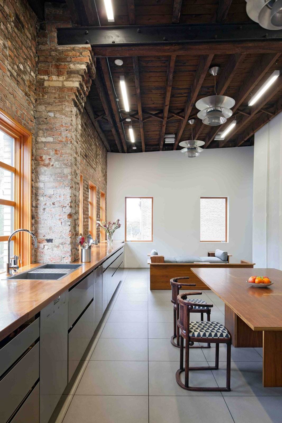 Kitchen, Wood Counter, and Pendant Lighting What the original building lacked in period detailing, it made up for with massive interior spaces, natural light, and a hardy palette of wood and raw brick.  Working with these loft signatures, David developed the hall's liveable side, adding under-floor heating, and a gigantic kitchen on the upper floor running the width of the building, with a 37-foot-long solid walnut counter on top of stainless steel cabinets. This unites the dining, cooking and social spaces that run the length of the front façade on the upper floor.  Photo 8 of 8 in This Spacious Home in a Former Warehouse is Part Art Gallery
