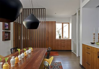 In the dining room, Beat Stout Black pendant lamps by Tom Dixon hang over a custom table by Edwin Blue.