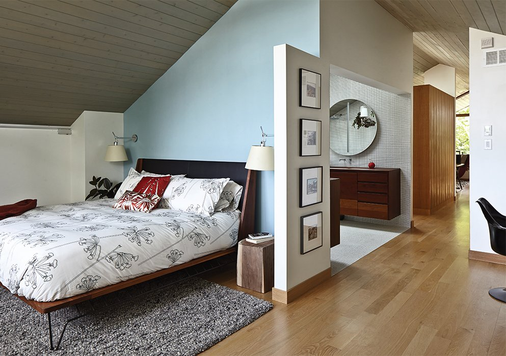 Bedroom, Bed, Night Stands, Lamps, Wall Lighting, Rug Floor, and Light Hardwood Floor In the master bedroom, a pair of Artemide Tolomeo sconces bookend a Matchbox bed by Edwin Blue.  Photo 8 of 10 in This Kansas City Home Looks Like Its Neighbors, But Reveals a Truly Modern Sensibility