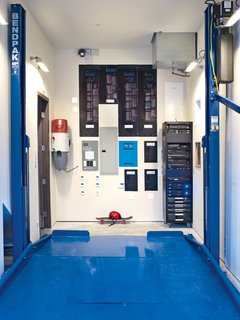 "In the garage, a collection of smart-home technology is on display alongside a Bendpak Auto Lift, which builder Bryan Henson calls ""an integral part of the house's design: With the lift in place we met the county's requirements for two covered parking spaces in a narrower garage bay. This freed up nearly 400 square feet of precious floor area on the other side of the house to accommodate both a mechanical room and a media room on the first floor.""<br><br>Other mechanisms include a Broan whole house vacuum system that keeps the indoor air free of dust and allergens; a Lutron HomeWorks system that controls lighting and shades; an ELAN g! home system that controls irrigation, lighting, and security; and an AM House home-entertainment rack."
