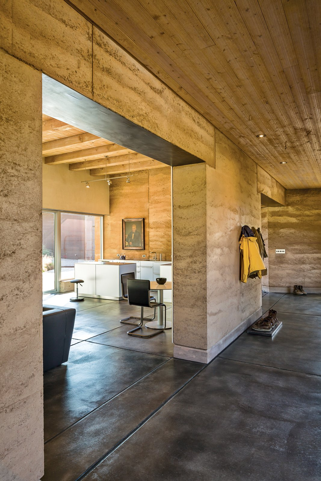 "Living Room and Concrete Floor Marrying the interior with the outdoors informed the design, as did the concept of subtraction: ""If you do it with two, then you can do it with one,"" Maniatis says, articulating Roger's algebra of minimalism. Photo by: Kirk Gittings  Photo 3 of 5 in A Sustainable Rammed Earth Home in New Mexico"