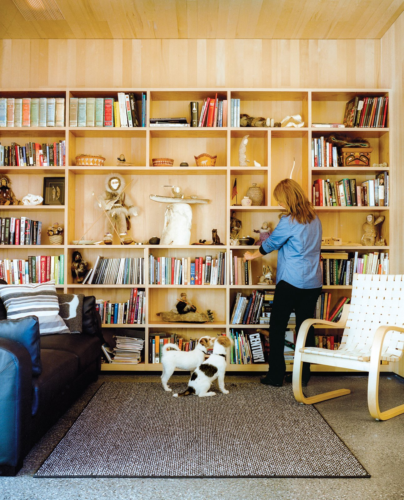 Living Room, Chair, Bookcase, Rug Floor, and Terrazzo Floor Architects Mayer Sattler-Smith designed the bookshelves and Alvar Aalto the 406 lounge chair for Artek.  Photo 9 of 20 in This Modern Cabin Is the Ideal HQ For a Family in Alaska