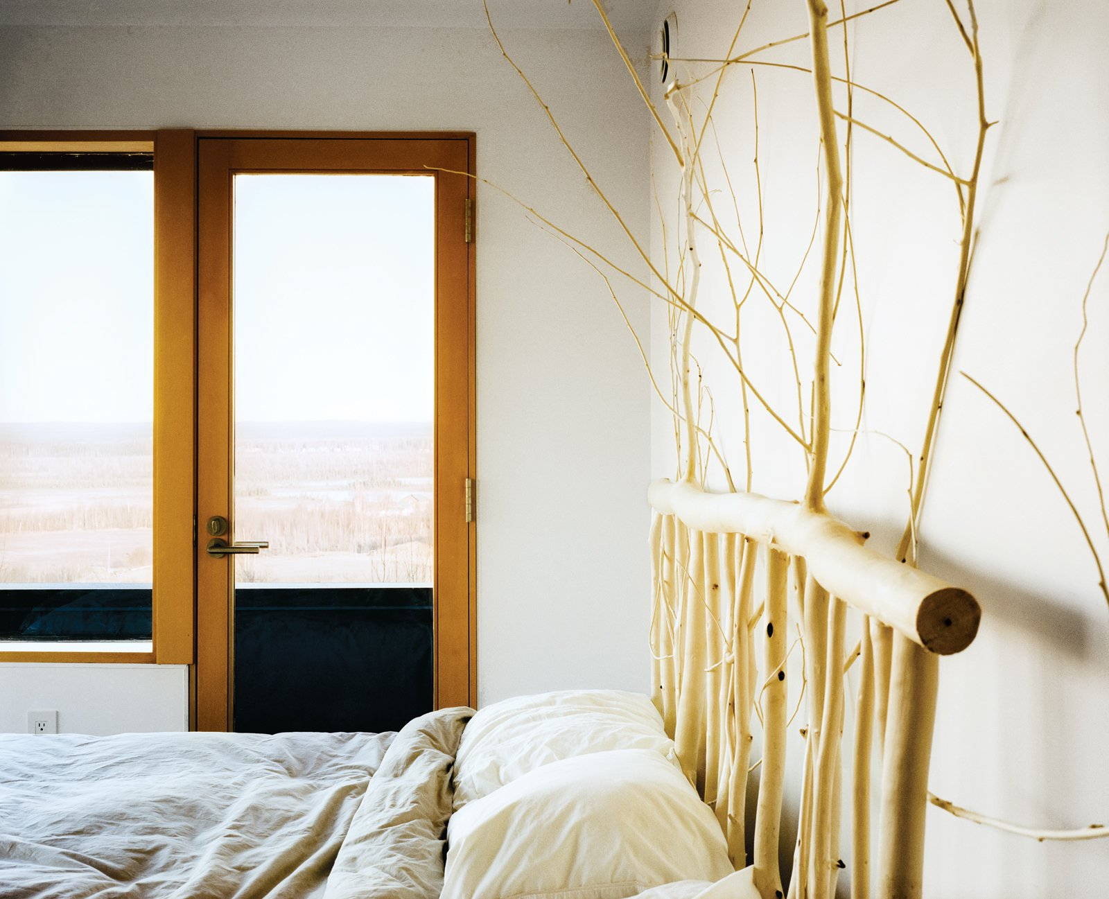 Bedroom and Bed Buser designed and made the headboard in the master bedroom from local aspens.  Photo 10 of 20 in This Modern Cabin Is the Ideal HQ For a Family in Alaska