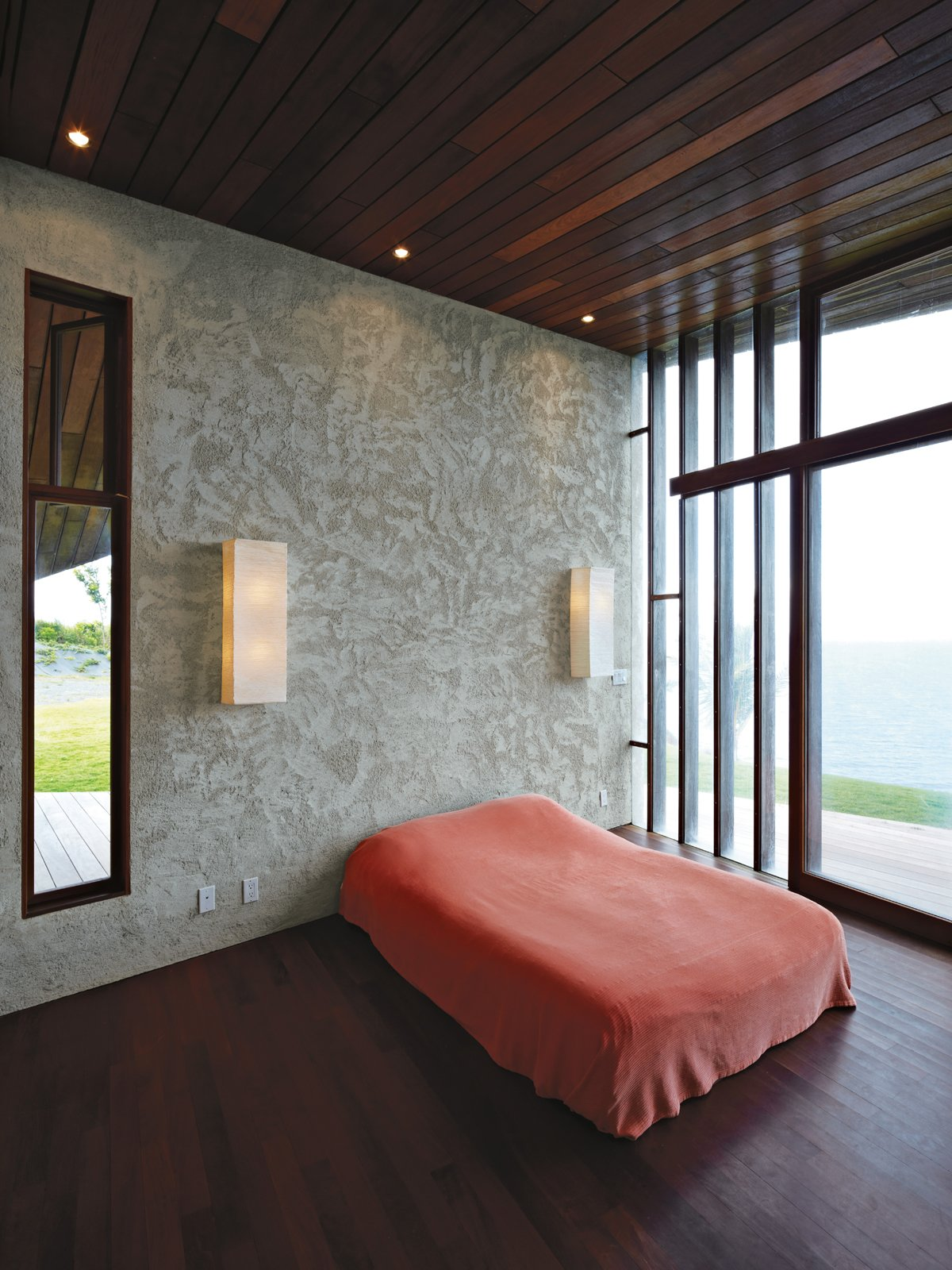 Bedroom, Bed, Dark Hardwood Floor, and Wall Lighting In the master bedroom, a basic platform bed and Ikea wall lights keep the attention on the ocean views afforded by the floor-to-ceiling windows.  Photo 9 of 10 in Clifftop House with Angled Roof in Maui