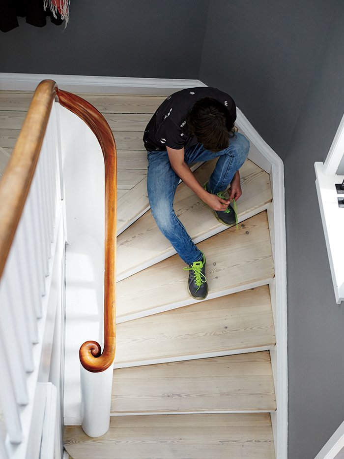 Staircase, Wood Railing, and Wood Tread Charrier's son, Fabian Fonnesbæk Charrier, 14, pauses on a staircase of white oil-finished pine floorboards.  Photo 3 of 12 in A Cramped Attic Became a Sunny Dining Room in this Renovation of a Copenhagen Tudor