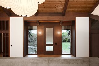 Midcentury architect Gene Zema, known for his Pacific Northwest mix of modernism and Japanese architecture, designed this house around 1974 to emphasize the texture and color of the exposed wood. Revitalized and renovated by SHED Architecture & Design, the stained-fir walls and beams contrast with the white walls, while simple paper light fixtures give it an elegant glow.
