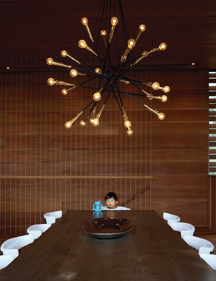 Dining Room, Chair, Table, and Pendant Lighting Wire stair balustrades create an airy vibe while reinforcing the linear wood detailing throughout. In the dining area, a Sputnik-style chandelier by Rewire in Los Angeles hangs above an oxidized maple table from BDDW and Clifford Pascoe chairs from Metropolis Modern.  Photo 2 of 9 in Modern Wood-Lined Family Home in the Hamptons