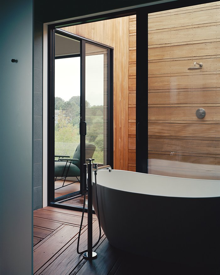 Bath Room, Freestanding Tub, Medium Hardwood Floor, and Open Shower The master suite's bathroom unfolds from a glass-walled bathing room, outfitted with a Signature Hardware tub and Lefroy Brooks fixtures, to an open-air shower.  Photo 5 of 9 in Modern Wood-Lined Family Home in the Hamptons