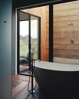 Designed by Hampton-based architecture firm Bates Masi, the master bathroom of this wood-lined house unfolds from a glass-walled bathing room. The space has been outfitted with a Signature Hardware tub, Lefroy Brooks fixtures, and an open-air shower.
