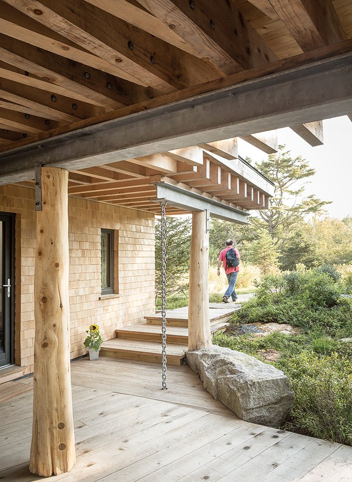 """Outdoor, Small Patio, Porch, Deck, Shrubs, Wood Patio, Porch, Deck, and Back Yard Angled beams are a fixture of the structure, both inside and out. The beams """"are an expression of the design, so they're reinforcing view lines,"""" Winkelman says, """"but they're also weaving together the different axes of the site.""""  Photo 4 of 7 in An Artist Builds a Wooden Home That Lets Nature Be the Boss"""
