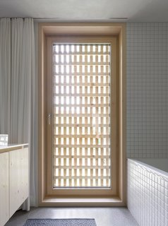 The latticework shell becomes a visual motif in the bathroom, furnished with appliances from Keramag, Kludi, and Laufen.