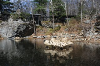 "The house and studio were christened ""Dragon Rock"" by their daughter Ann who said the rock formation resembled a dragon sipping from the pool. The pool was created by feeding a waterfall into to the pit. Seen here is a floating sculpture by current artist-in-resident Stephen Talasnik."