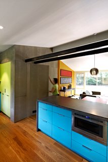 A dark concrete counter and blue laminate cabinets surround the Jenn-Air microwave drawer in architect Janet Bloomberg's kitchen. The pendant hanging above the table is a Tejido Round Suspension from Artemide.
