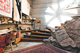 A handful of operations staff live in on-site apartments. Rather than dig out a boulder that's part of the mesa Arcosanti rests upon, builders incorporated it into the room. Woodworker Tim Daulton constructed the staircase.<br><br>Photo by: Peter Bohler